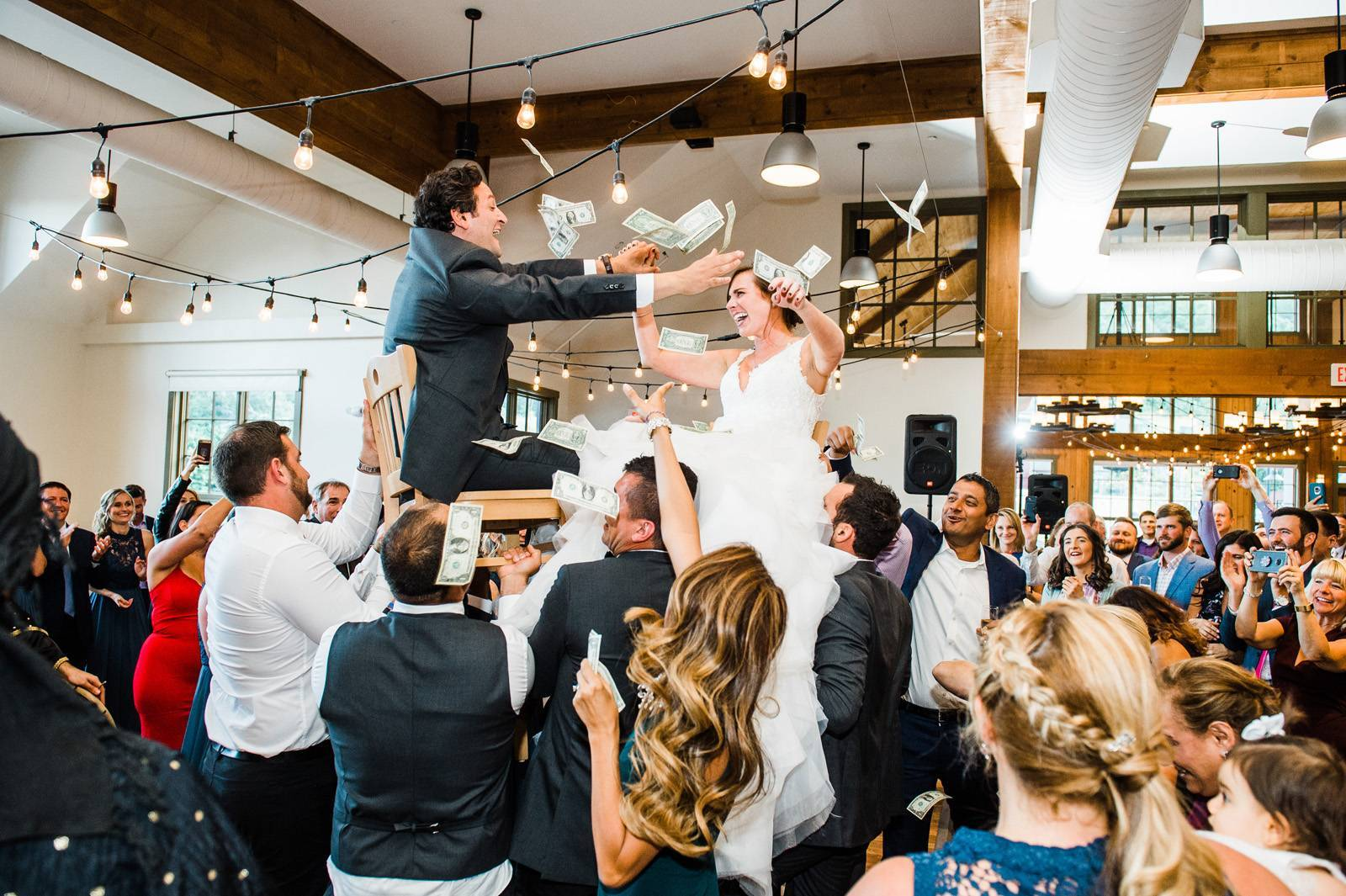 Bride and groom hoisted in chairs at reception by guests