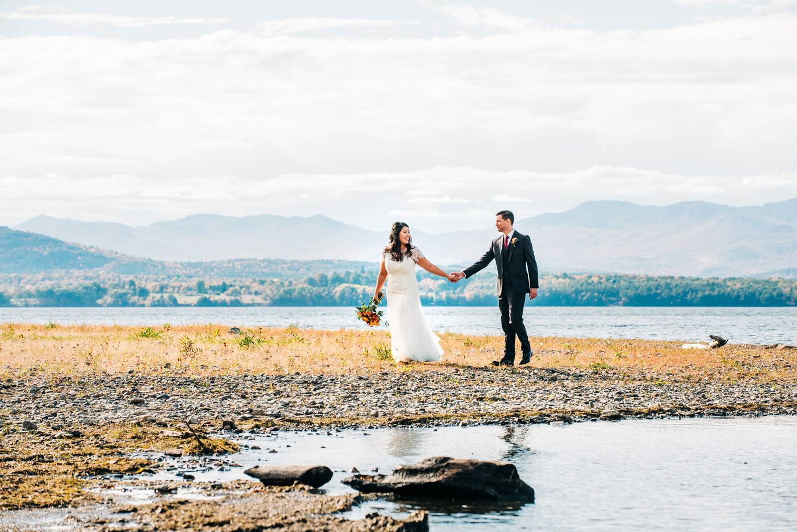 Bride and groom portrait walking along water's edge with mountains in background