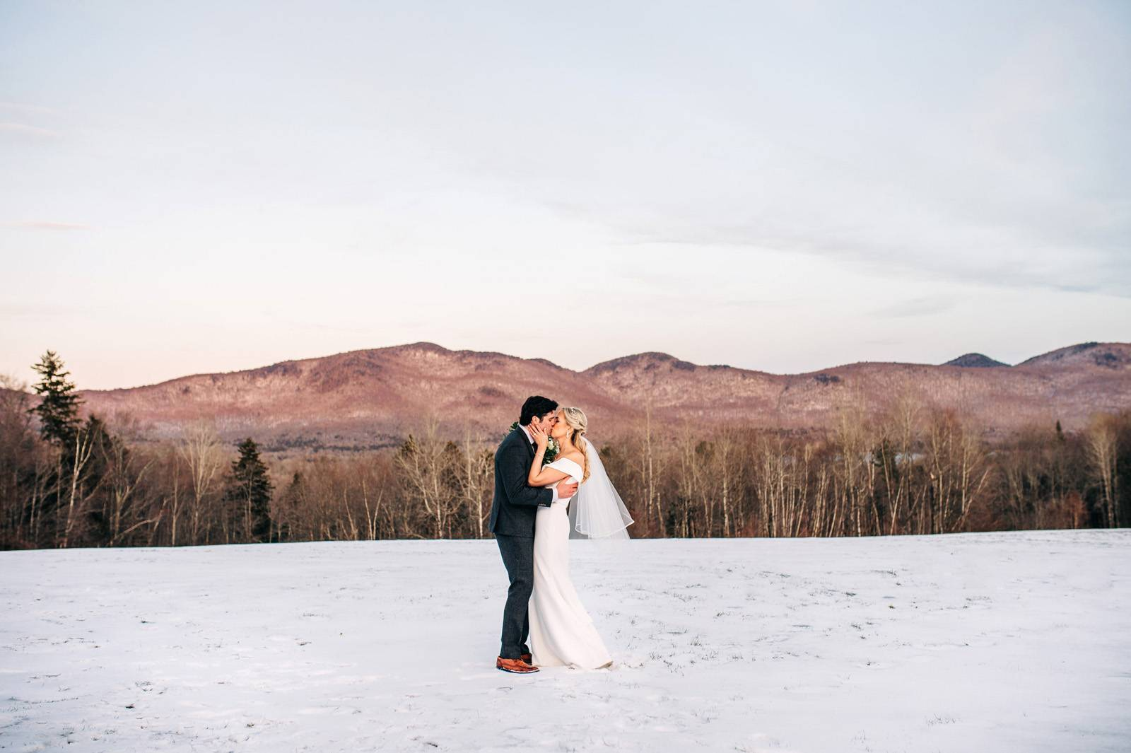 Bride and groom kissing in the snow with mountain backdrop
