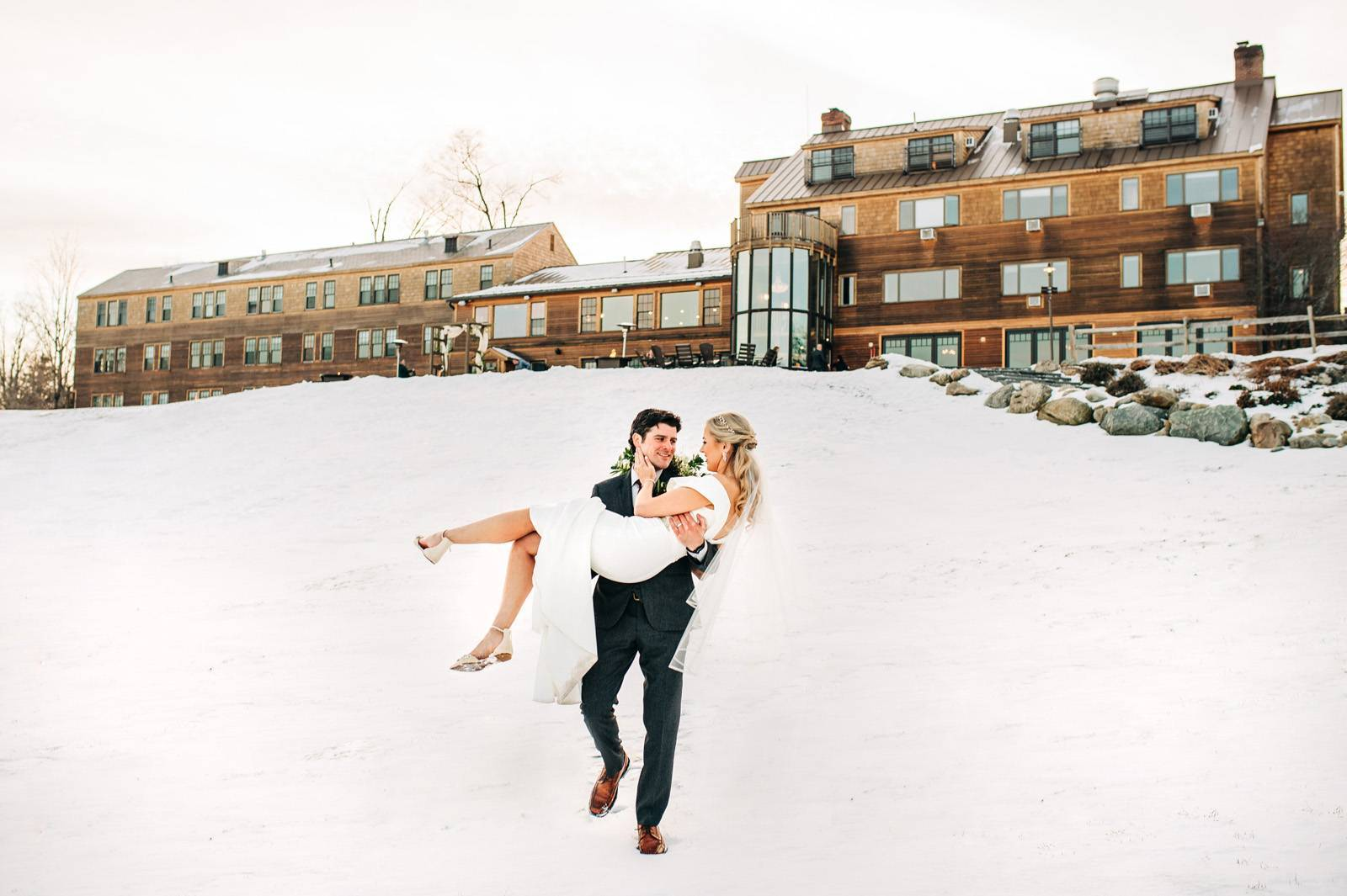 Groom carrying bride down the hill in the snow for winter wedding