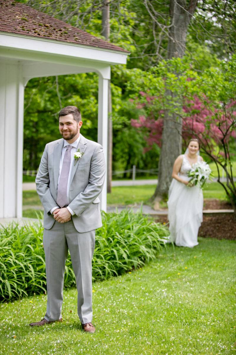 Bride sneaking up behind groom for first look at Basin Harbor summer wedding