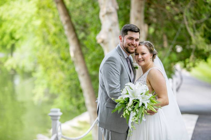 Portrait of bride and groom during summer wedding; bride holding white lily and greenery bouquet