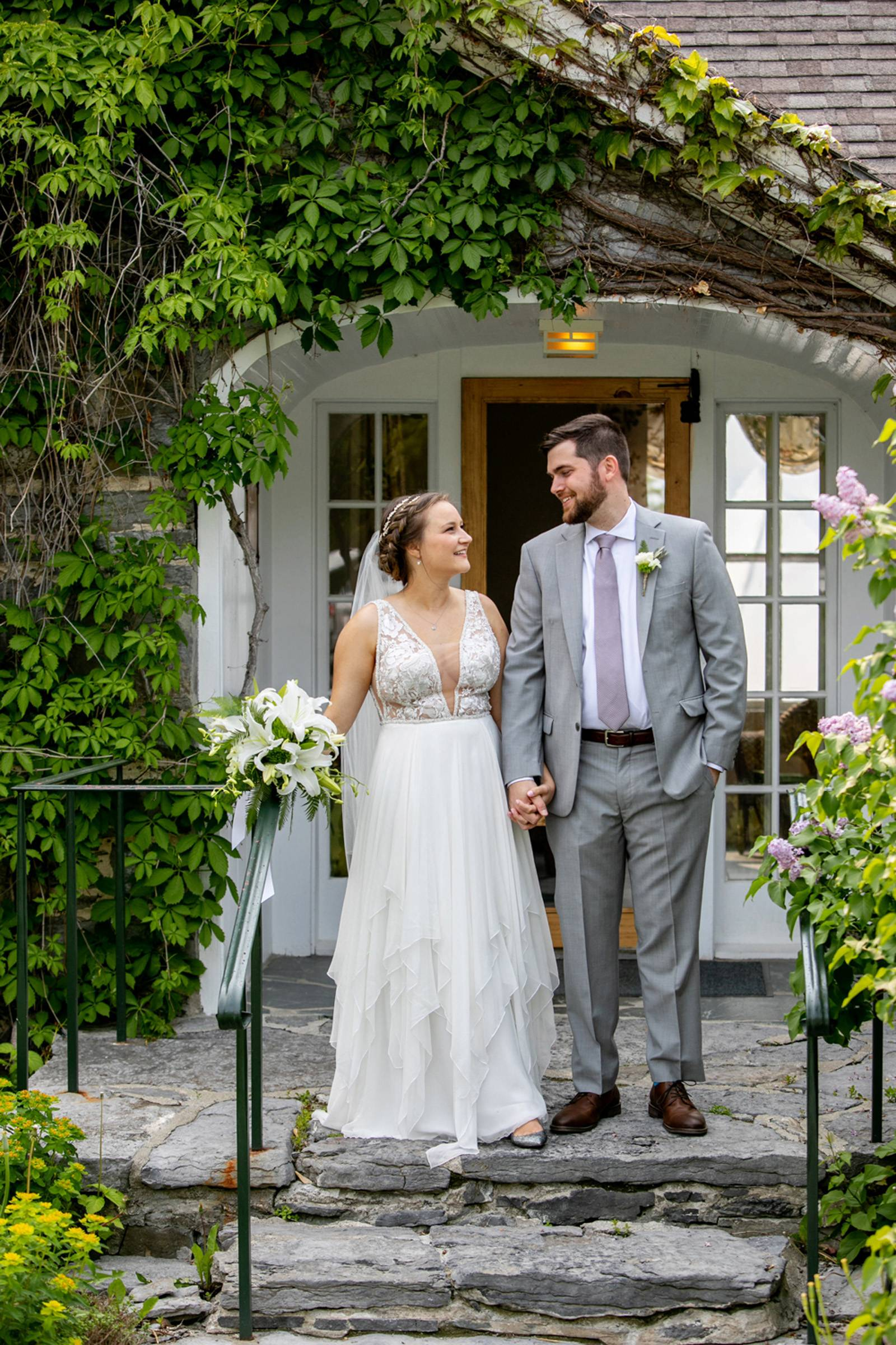 Bride, wearing lace top and chiffon bottom gown, smiling at groom