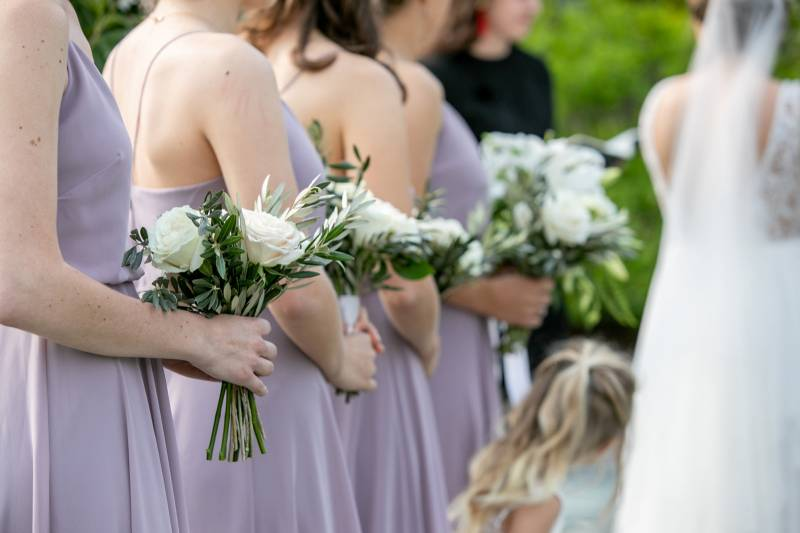Bridesmaids wearing lavender dresses and carrying white and greenery bouquets
