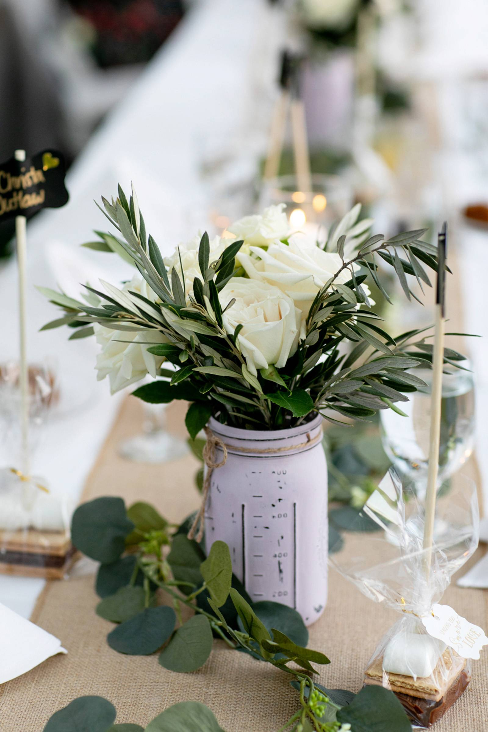 Lavender painted mason jars with rosemary and white flowers
