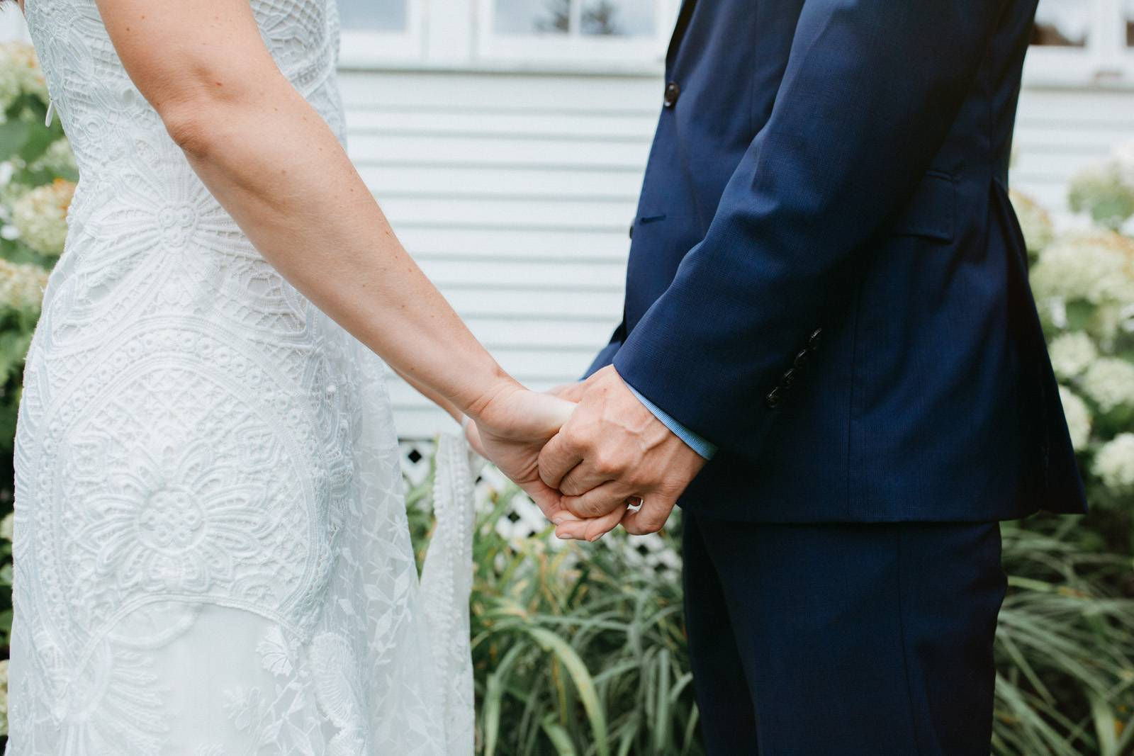 Close up of bride and groom holding hands, showcasing bride's lace dress