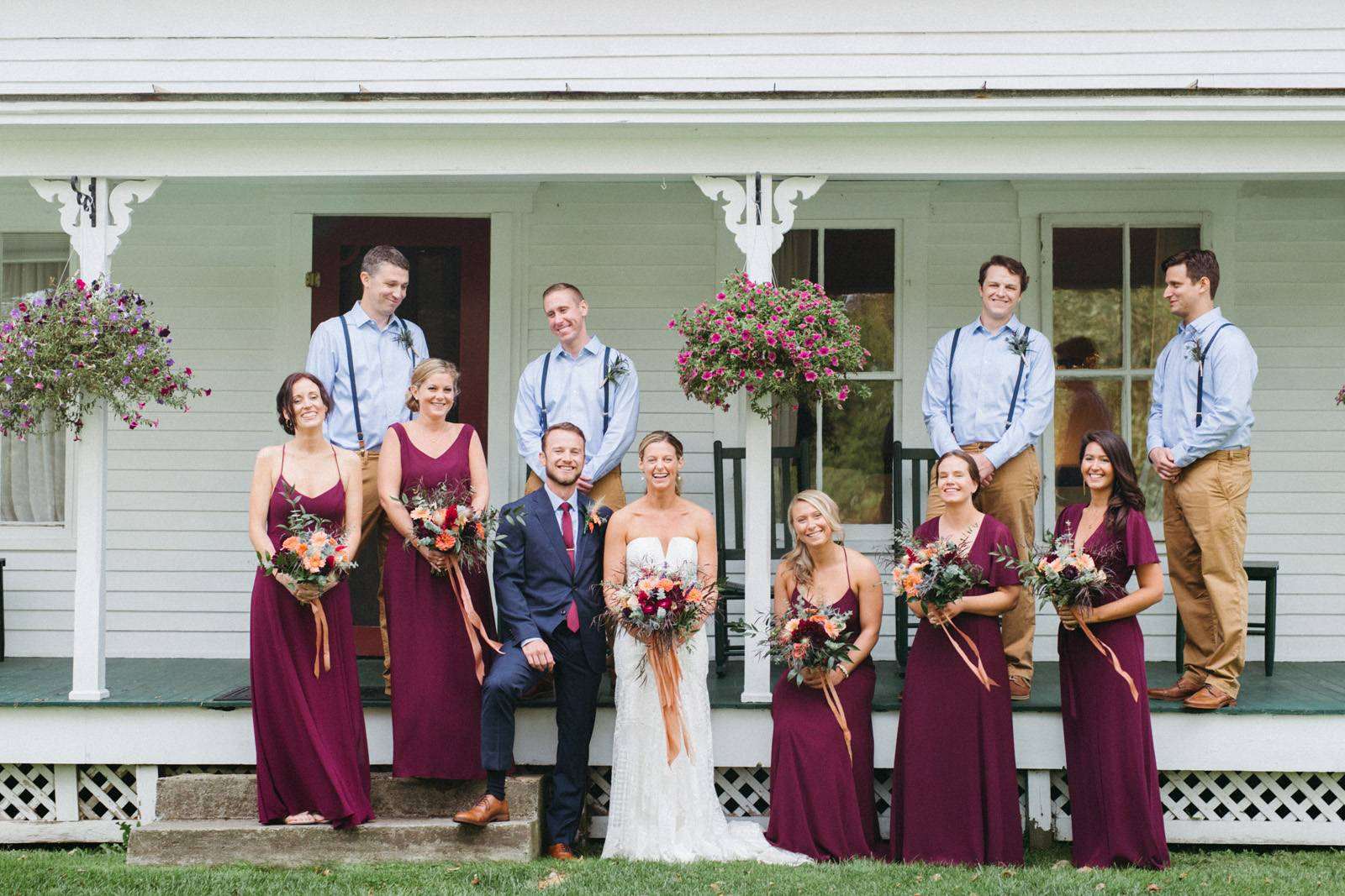 Portrait of wedding party with bridesmaids in burgundy dresses and groomsmen wearing blue shirts and
