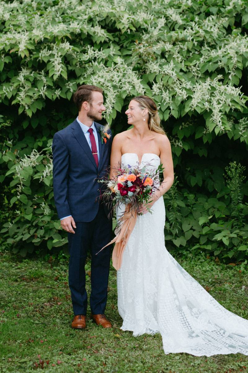 Portrait of groom and bride, holding lush moody bouquet and wearing boho lace dress