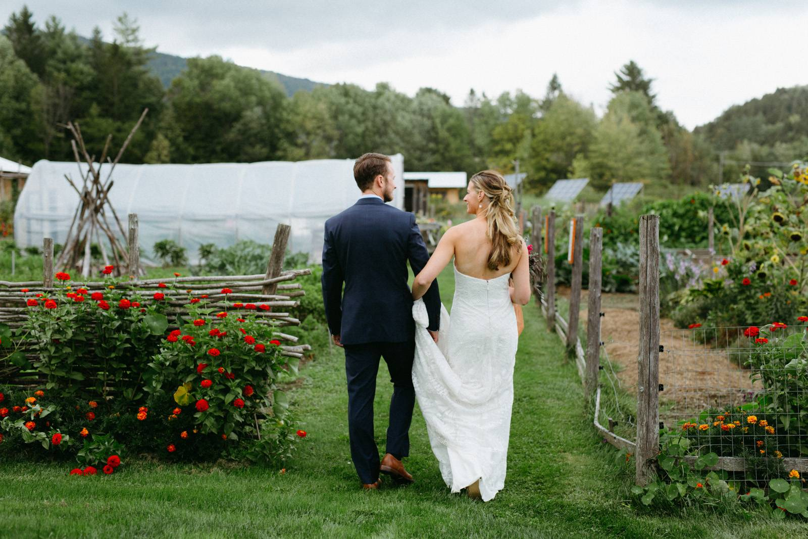 Bride and groom walking through farm at Lareau Farm Inn in Waitsfield Vermont