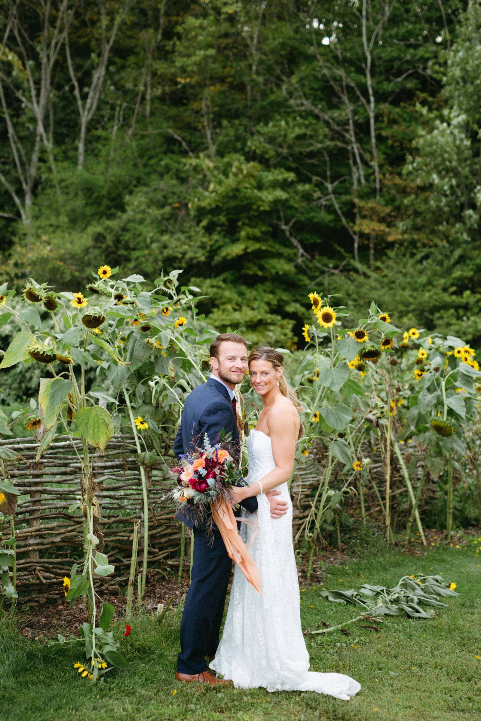 Bride and groom portrait in front of sunflowers