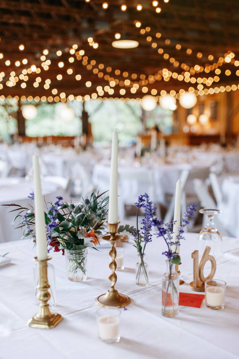 Organic flowers and mismatched vintage candlesticks table setting at Lareau Farm Inn wedding recepti