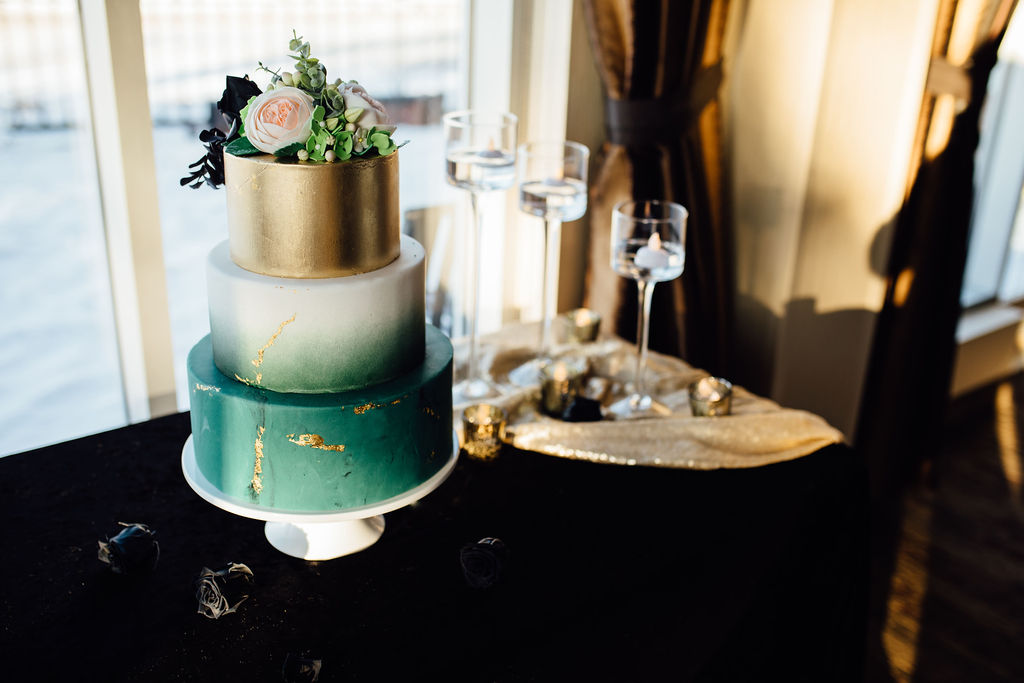 Three tier wedding cake with cold top and marbleized emerald and gold layer