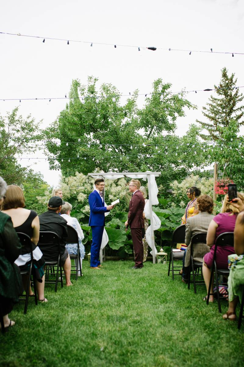 Grooms saying their vows at a garden wedding