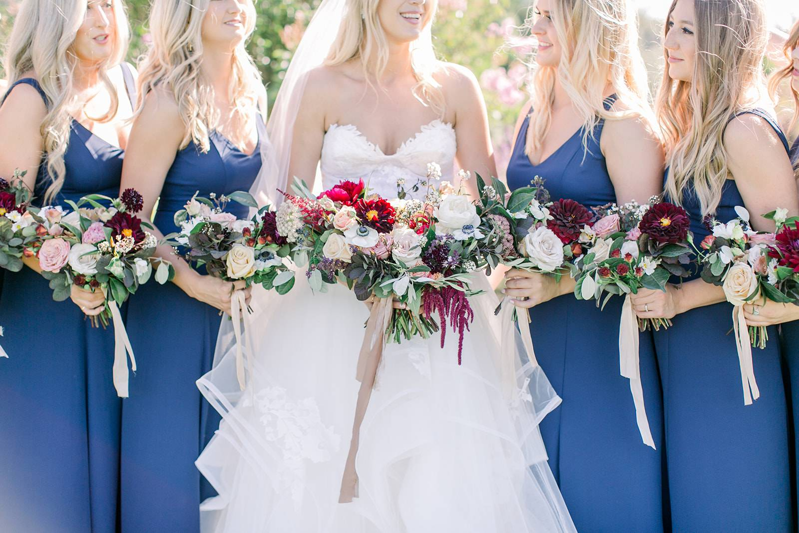 Carly is Standing with Her Bridemaids and Holding April Flowers | The Wedding Standard