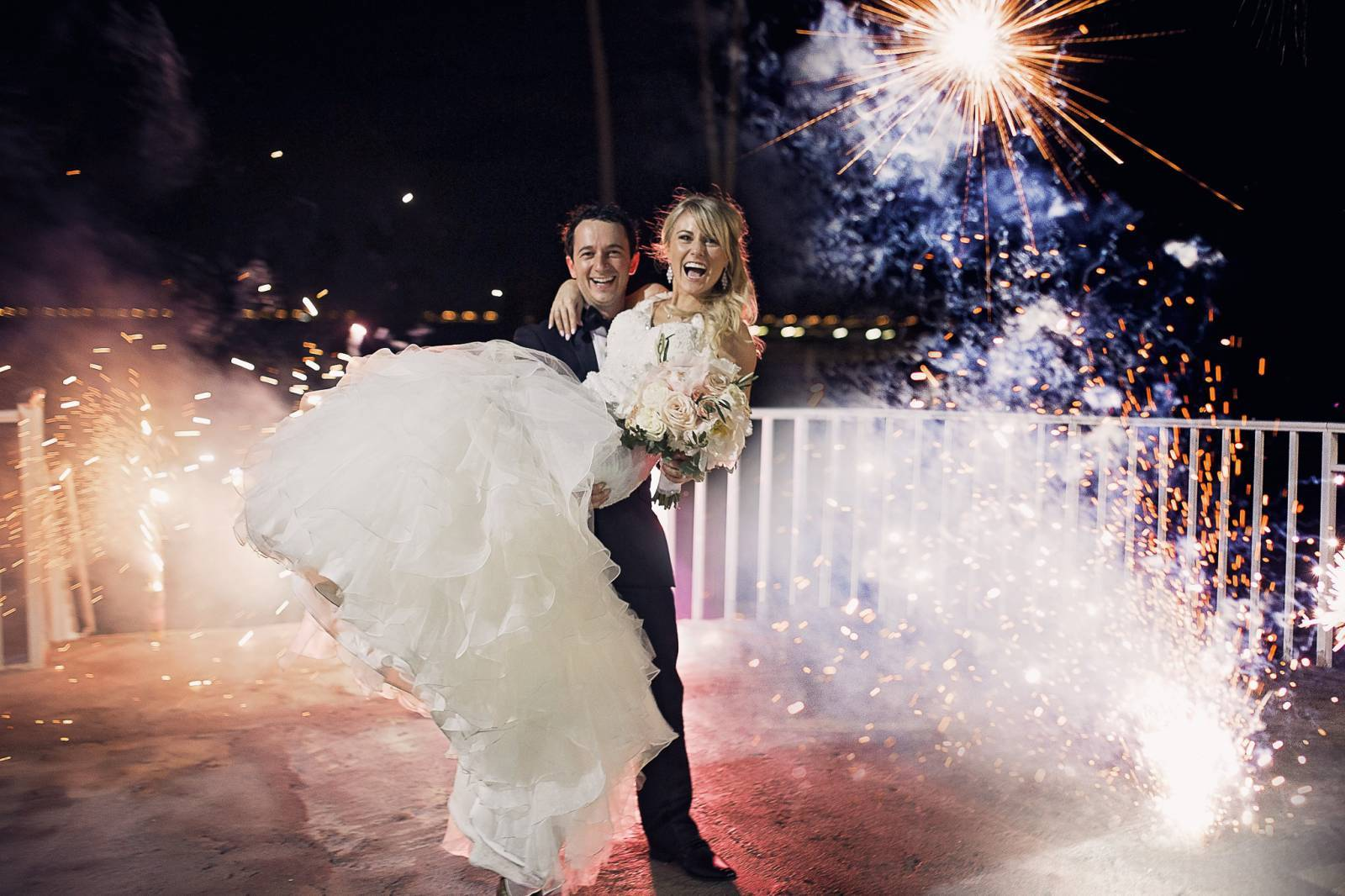 portrait of bride and groom under fireworks celebrating their wedding captured by Cat Lemus Photogra