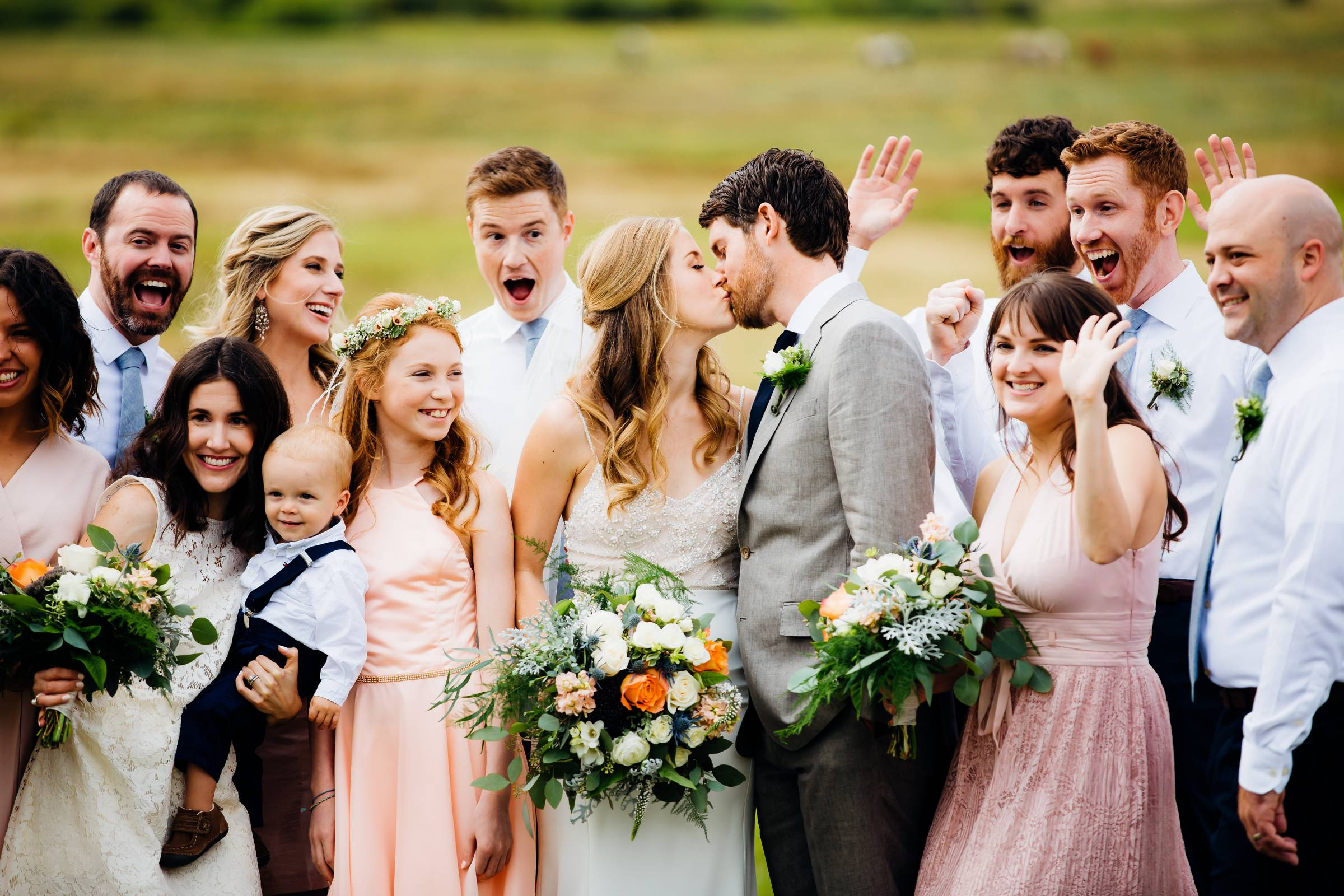 bride and groom kissing with wedding party | Rocky Mountain wedding planned by Glow Events