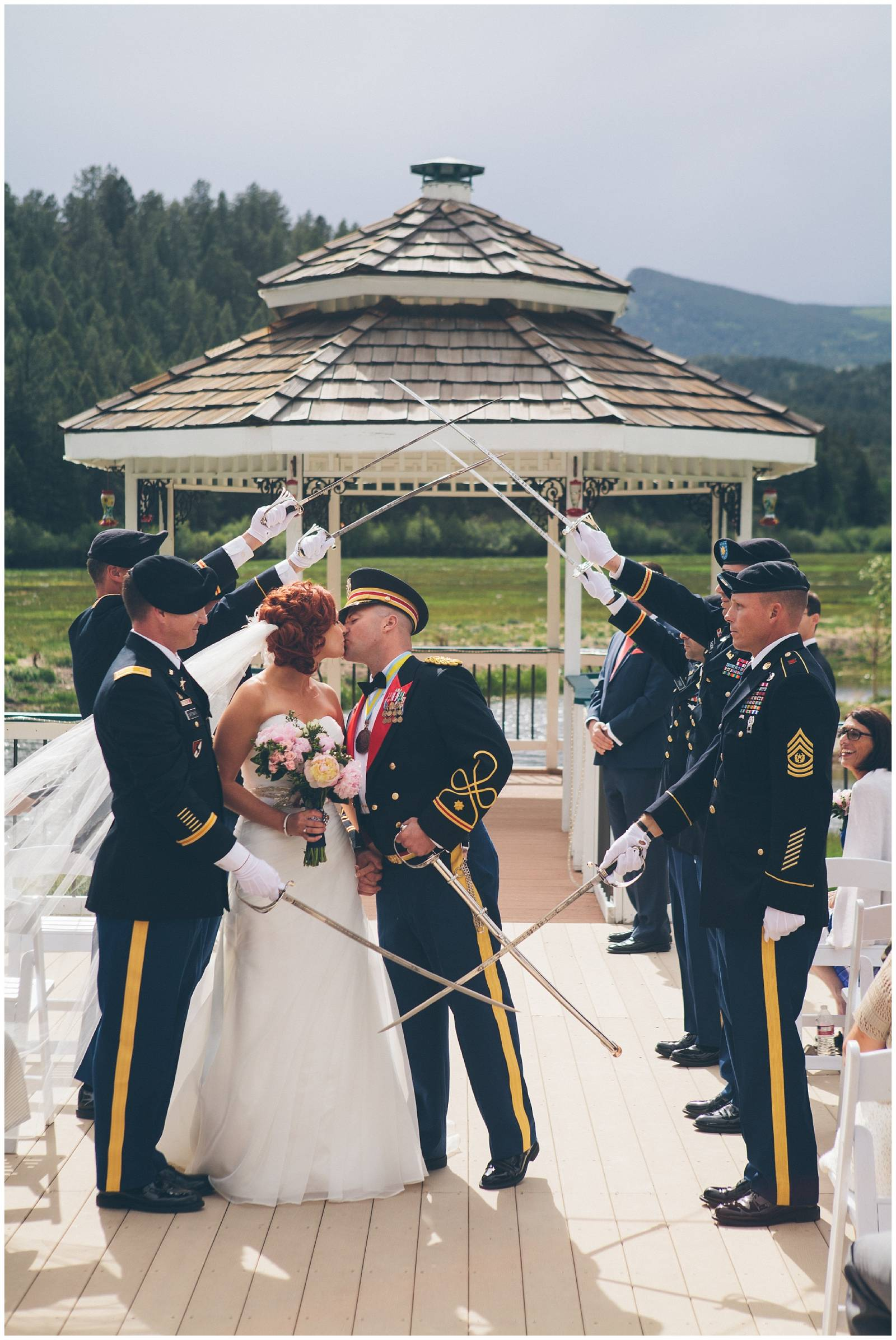bride and groom walking through military swords | mountain wedding ceremony designed by Glow Events