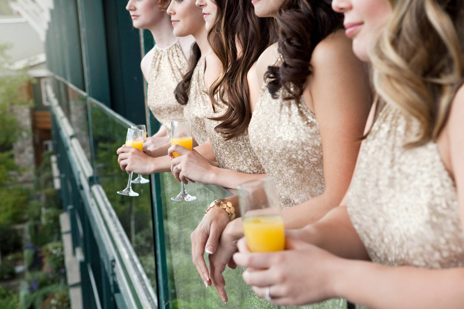 bridesmaids in gold dresses drinking mimosas captured by Tana Photography