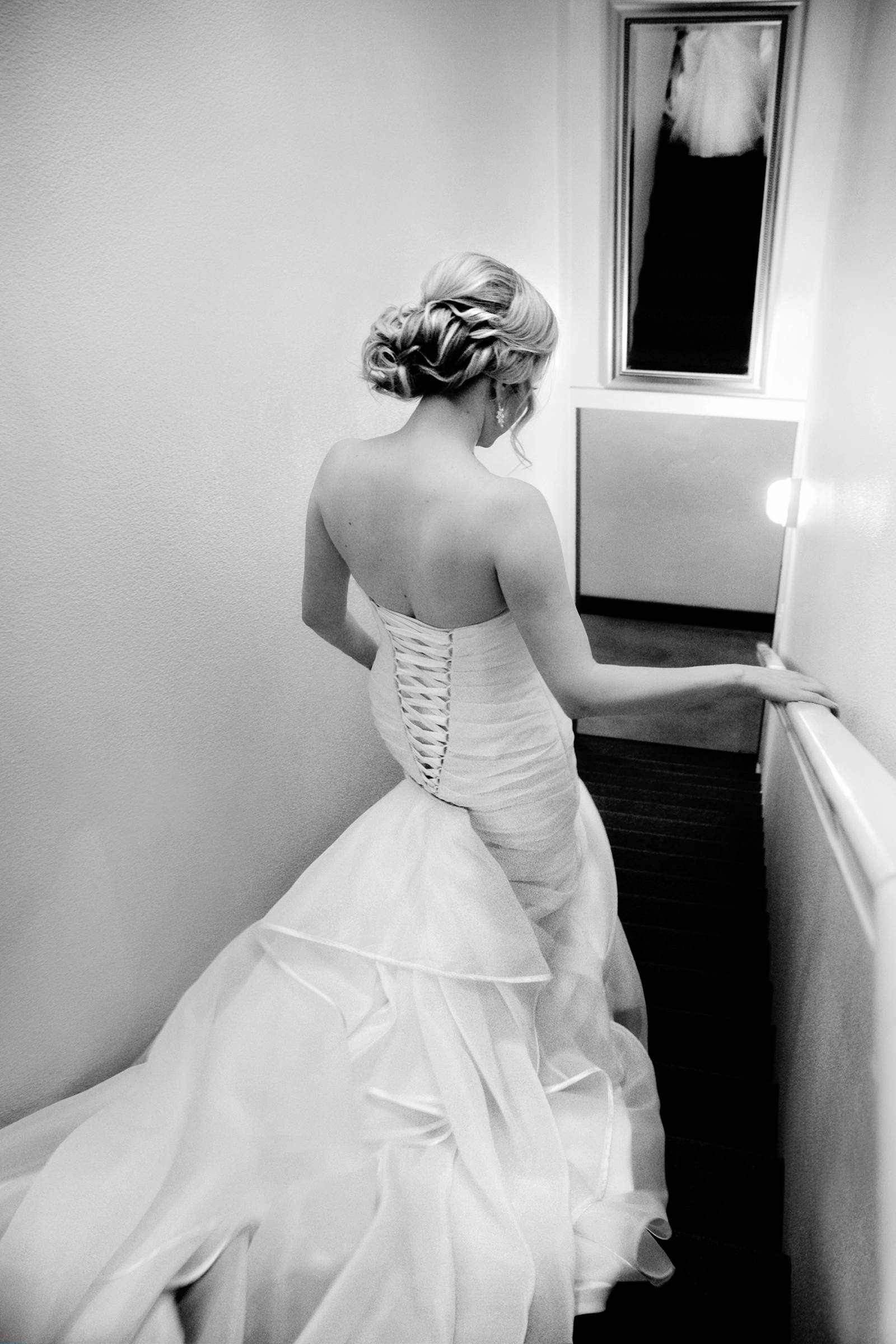 Tana Photography captures black and white photo of bride walking down stairs in wedding dress