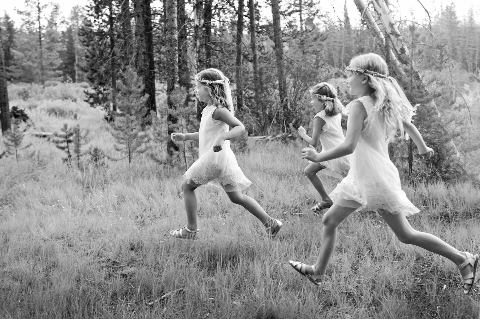 Tana Photography captures flower girls from wedding running through the forest