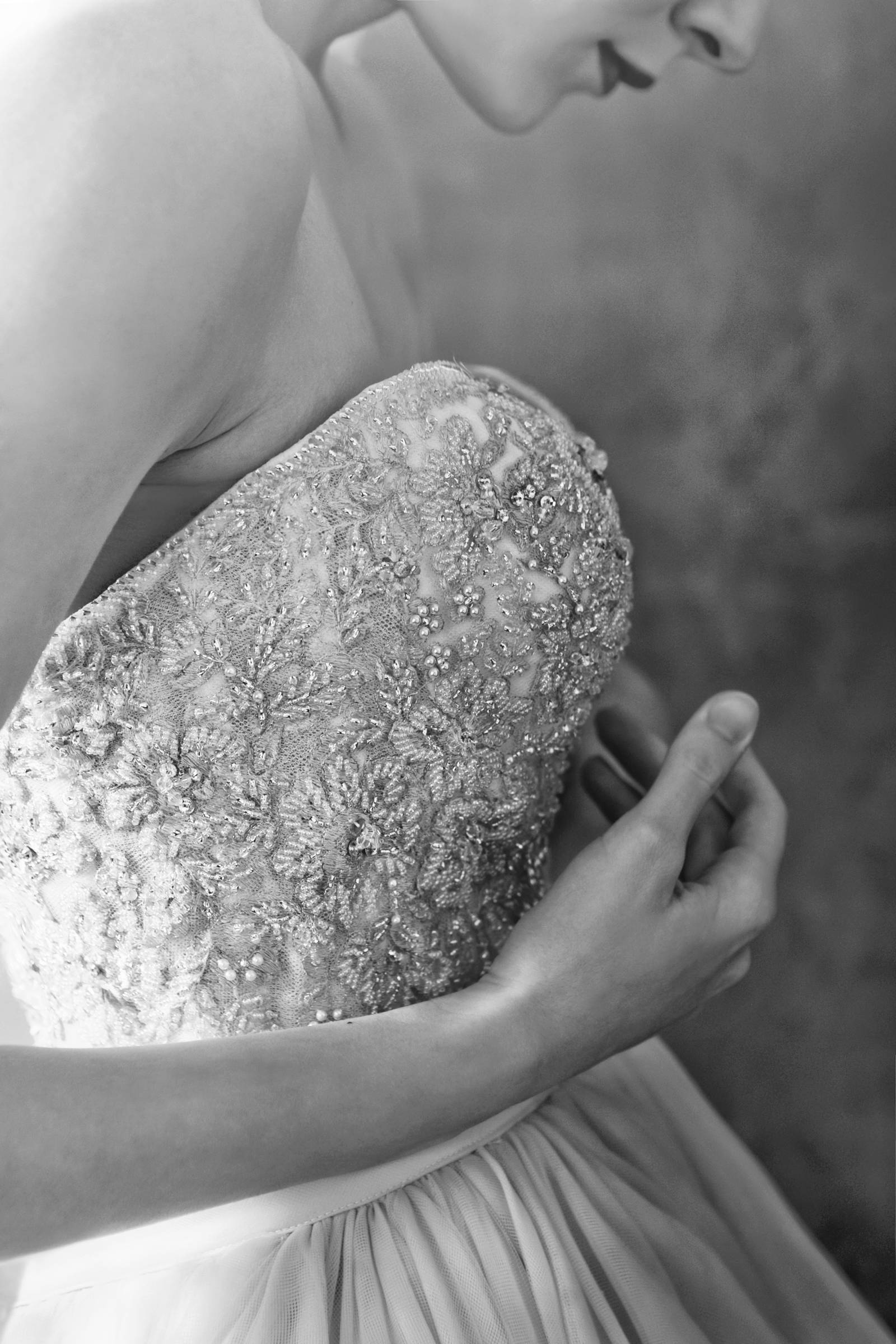 black and white photograph by Tana Photography | details of beaded wedding dress on bride