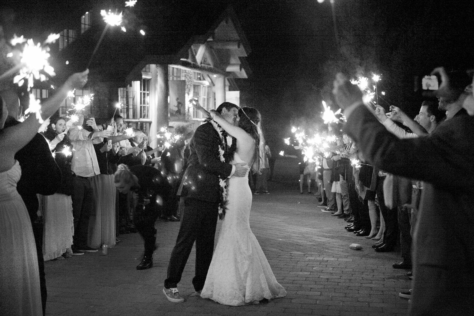 bride and groom kissing under guests holding sparklers | Tana Photography