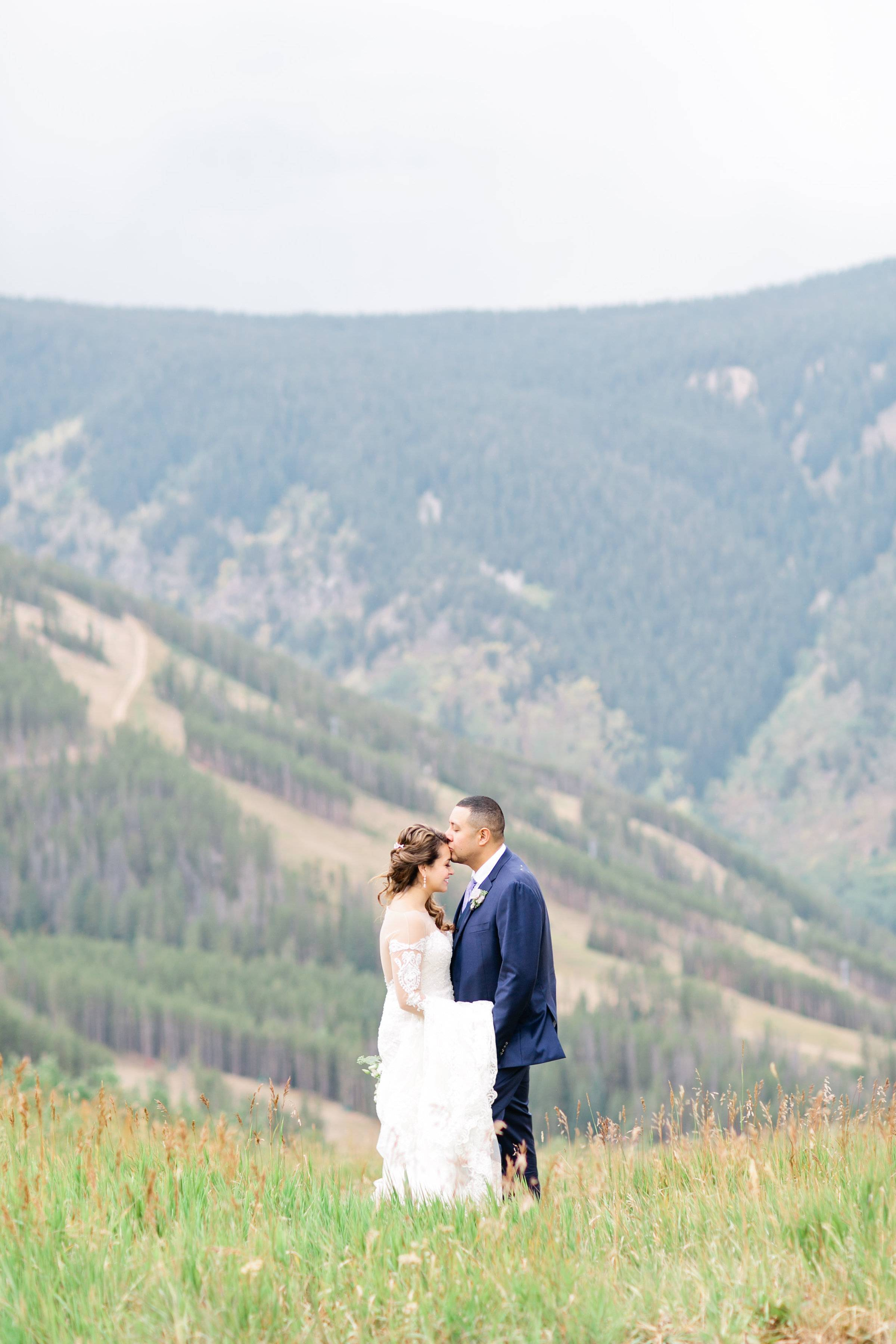 destination Rocky Mountain wedding | bride and groom kissing | Colorado wedding planned by Revel & R