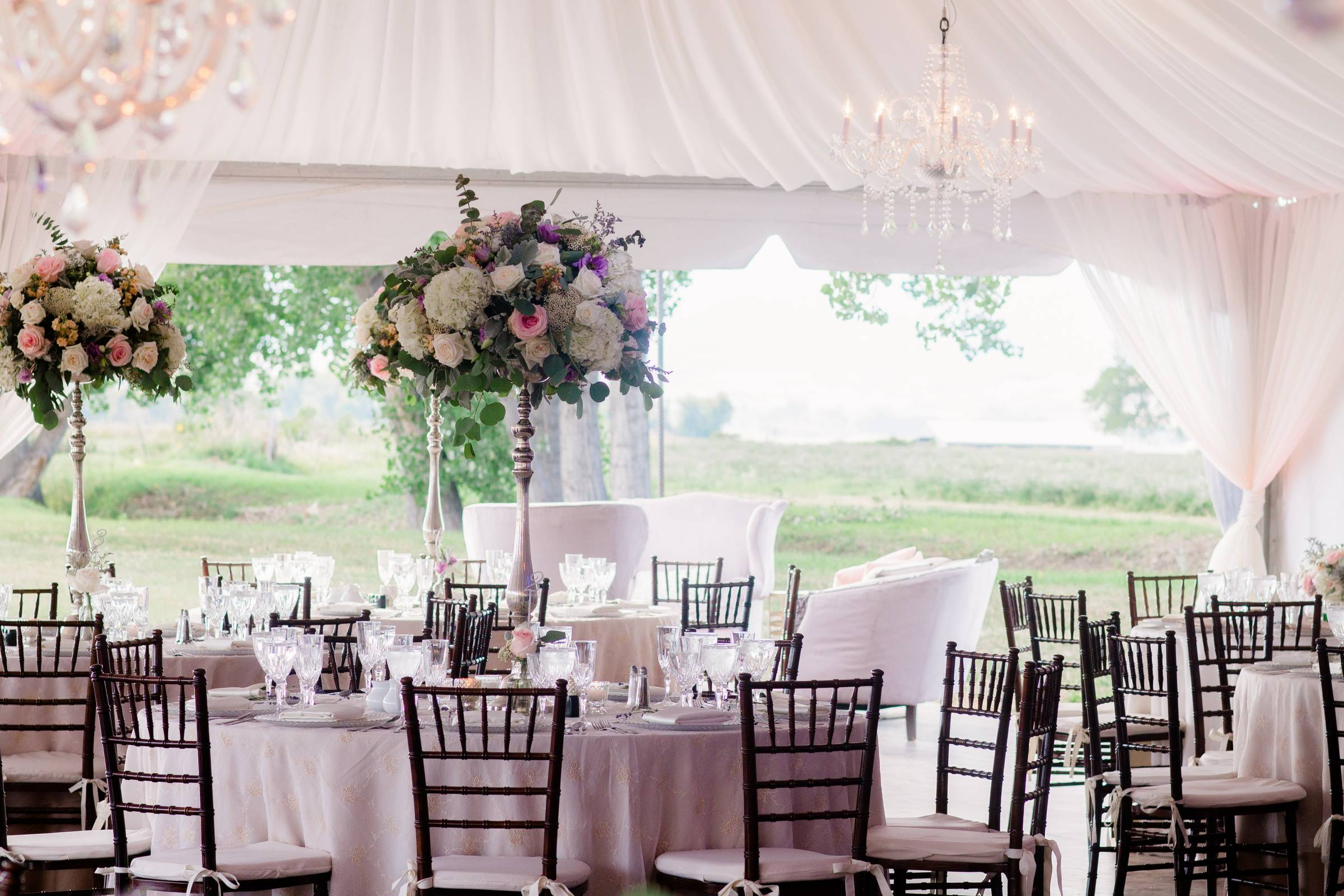 wedding reception planned by Revel & Roots Events | pink table cloths and large floral centerpieces