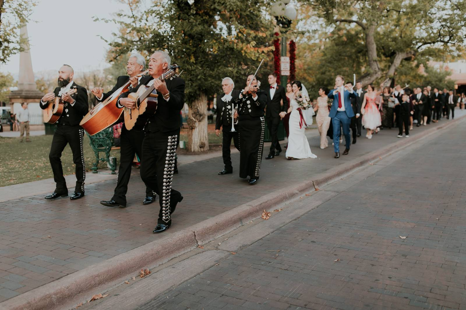 mariachi band leading bride groom and wedding guests around the block