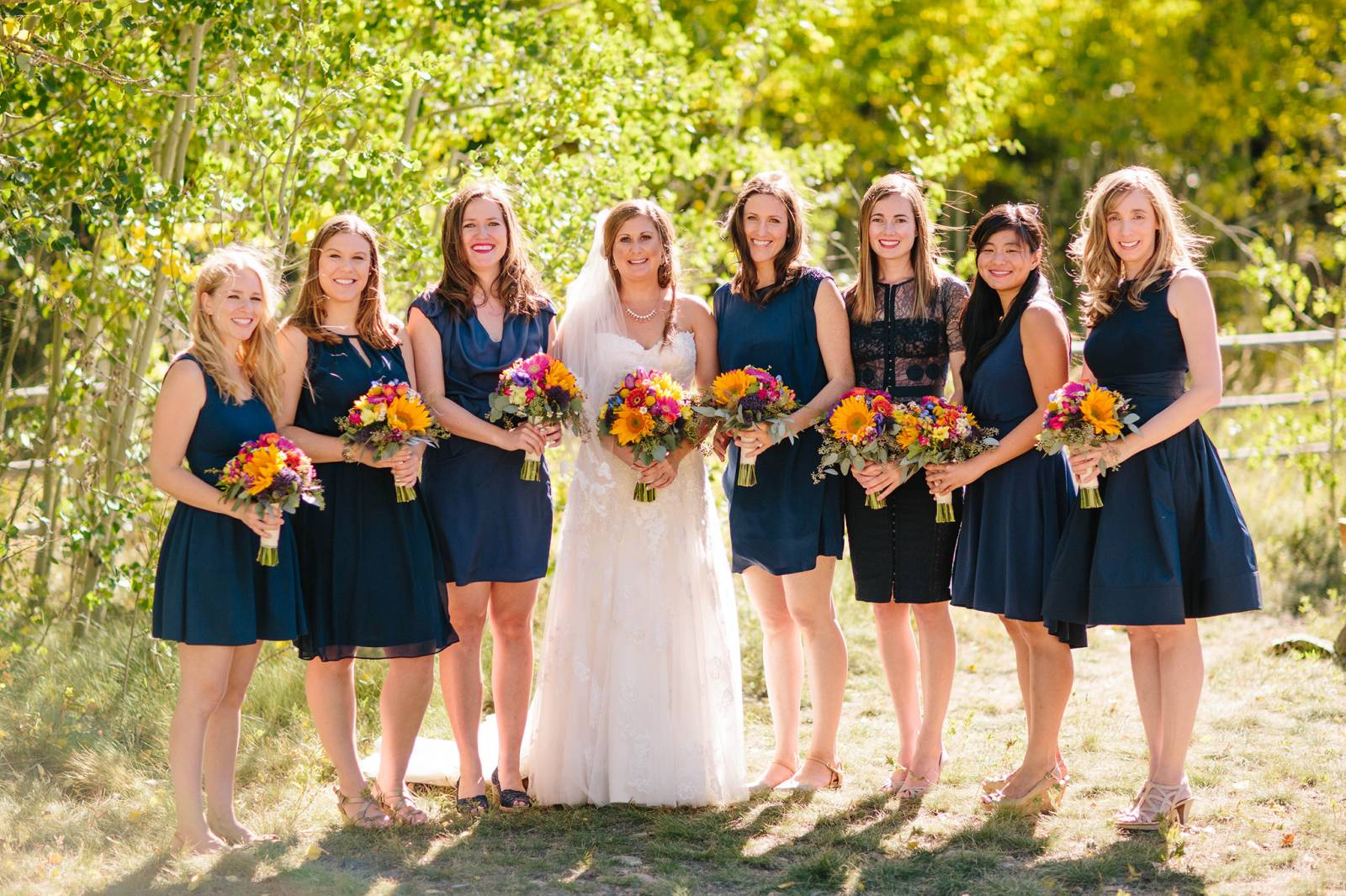 bride and bridesmaids in short navy blue dresses holding summer floral bouquets at the Wild Basin Lo