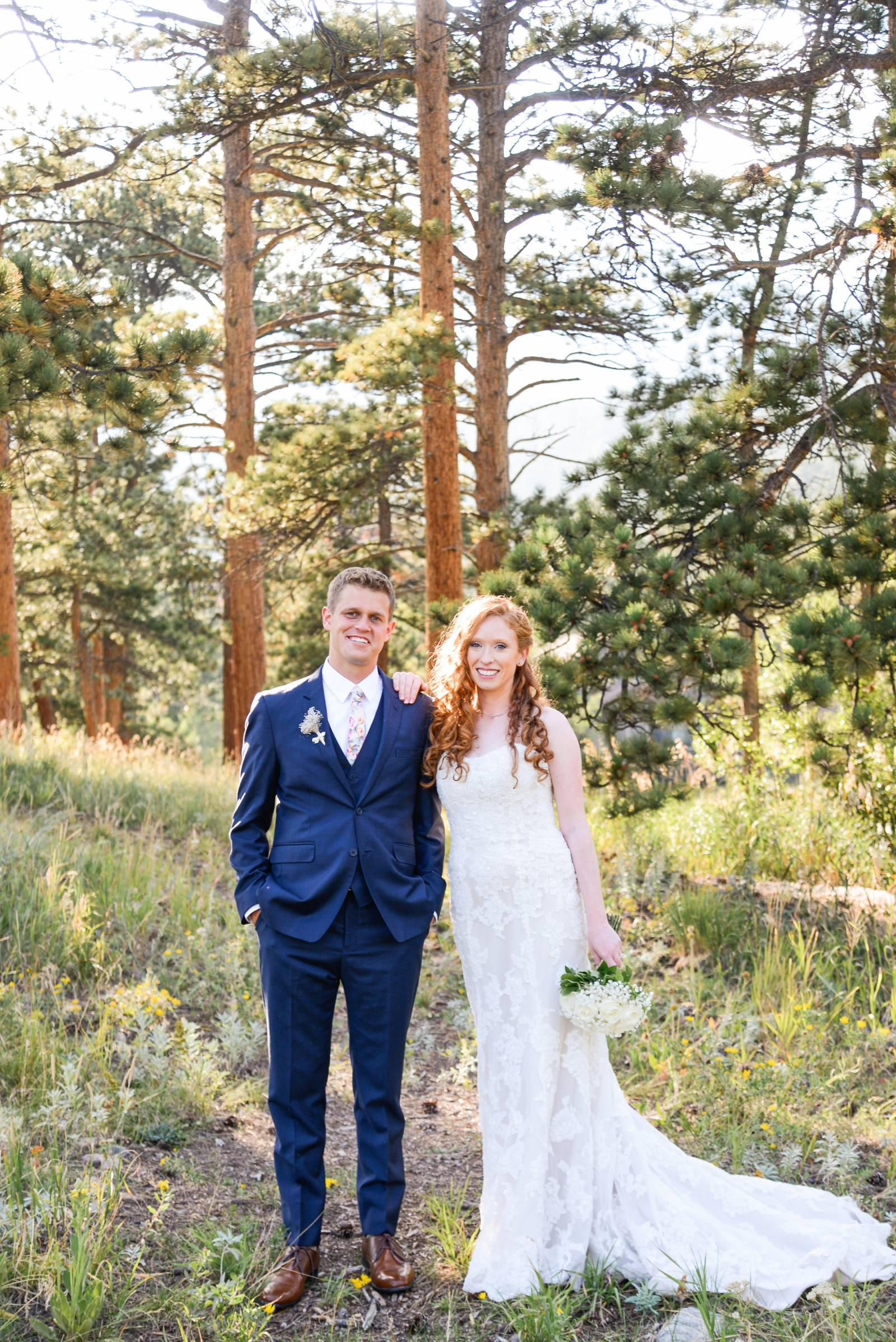 redhead bride with groom standing in an Estes Park, Colorado forest outside at the Wild Basin Lodge
