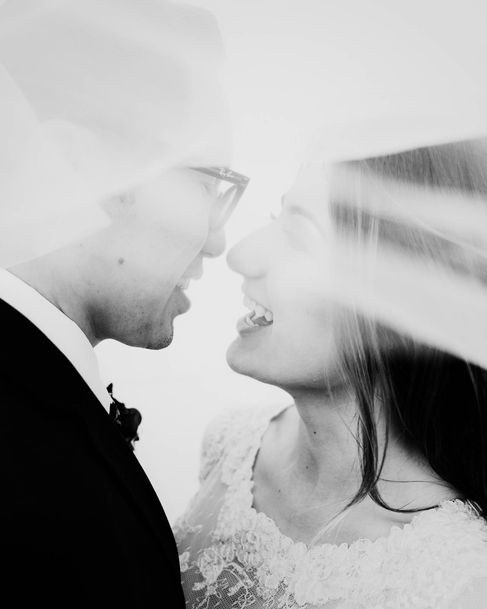black and white portrait of bride and groom under the bride's veil captured by Thistle & Pine Creati