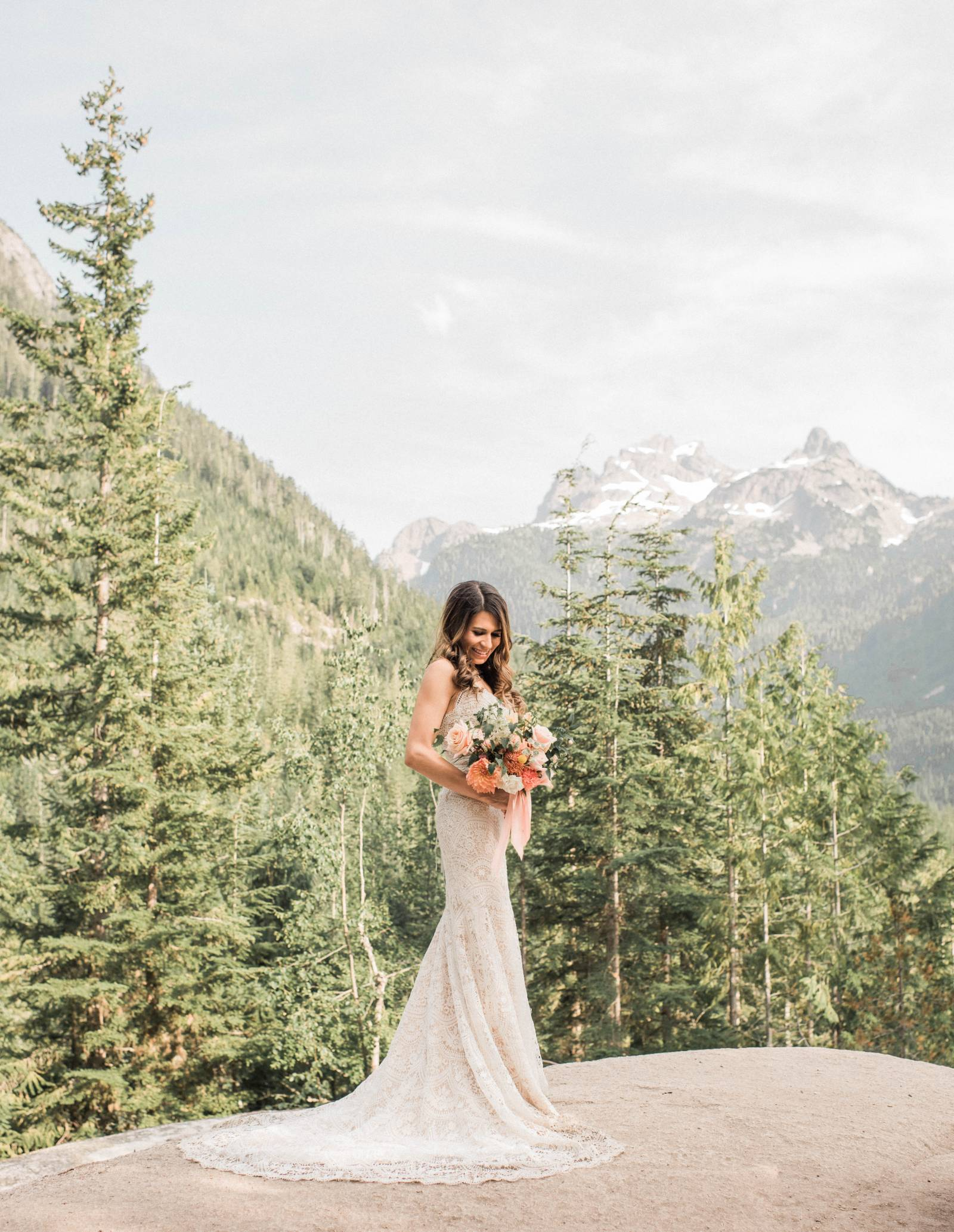 bridal portrait on top of British Columbia mountain | bride holding a spring bouquet