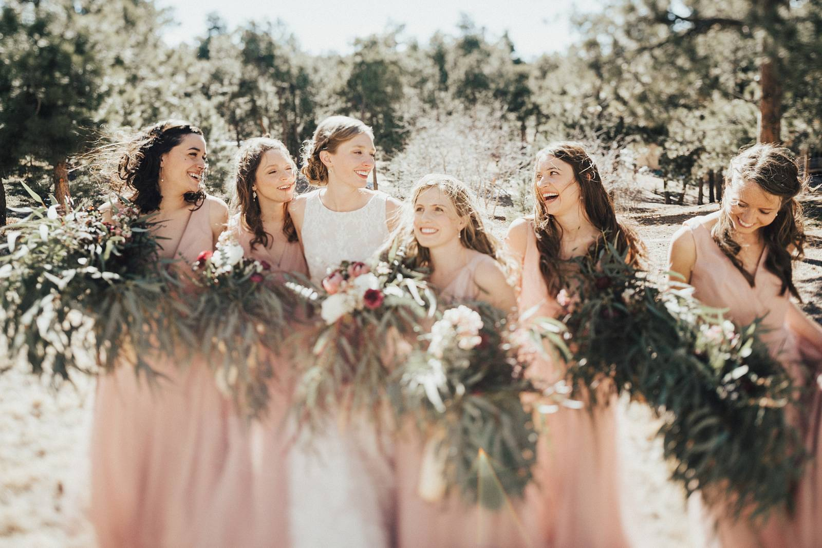 bride with bridesmaids in blush colored dresses