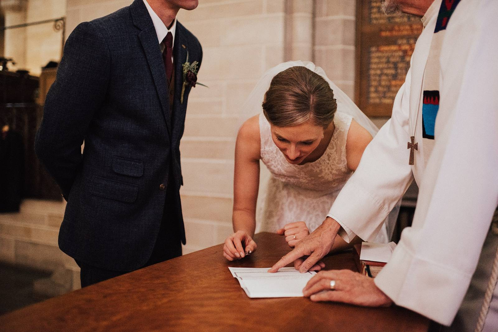 bride and groom signing wedding certificate