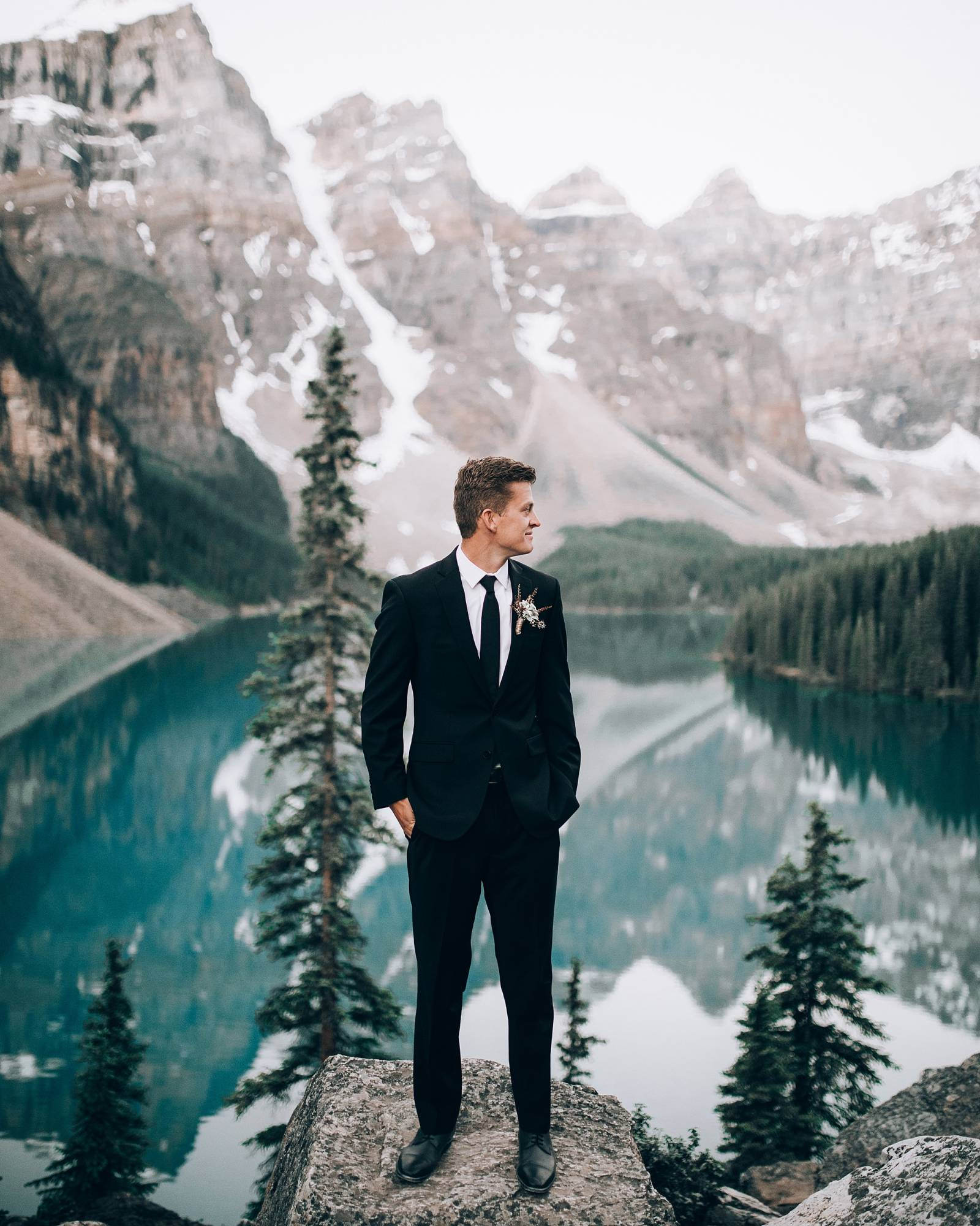 classic groom style | black tux | stunning mountain portrait of groom | Lake Louise, Alberta wedding