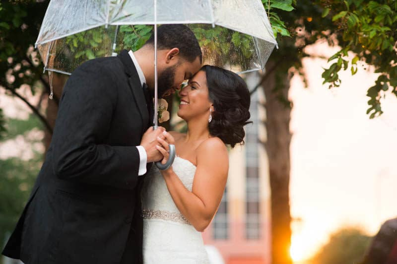 Couple face to face smiling under a clear umbrella