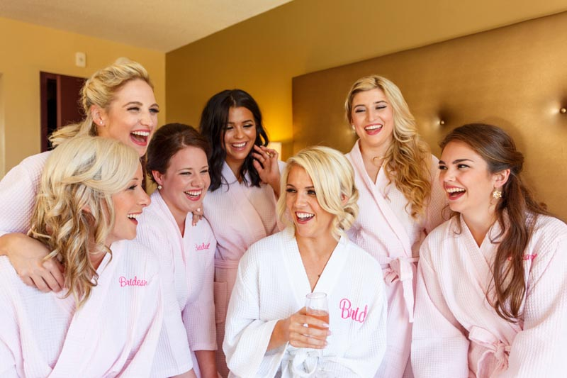 bride and bridesmaids laughing in robes