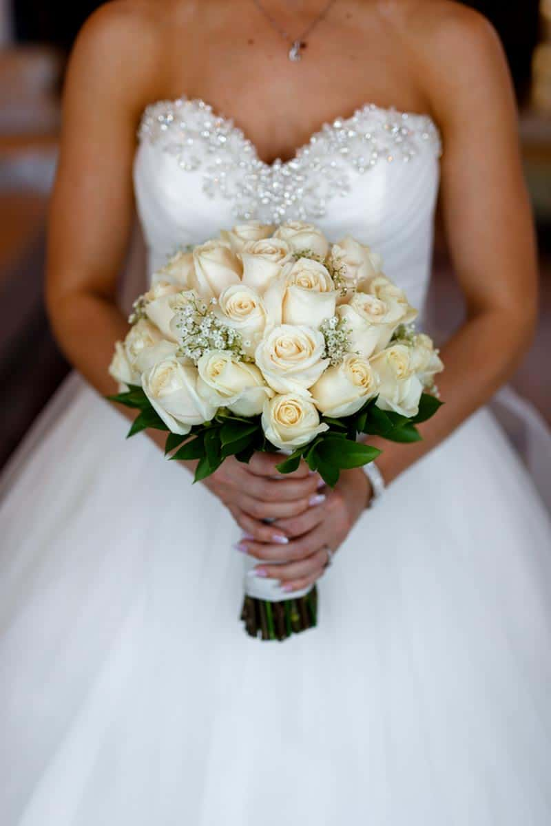 bride holding white rose and baby's breathe bouquet