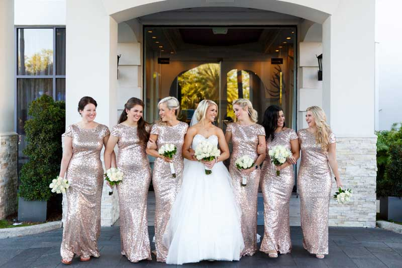 bride walking with bridesmaids in gold sequin dresses