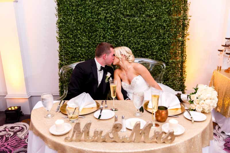 bride and groom kissing in front of hedge wall at sweetheart table