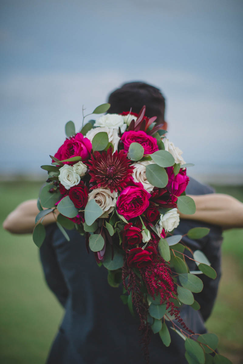 bridal hugging groom while holding cascading bouquet