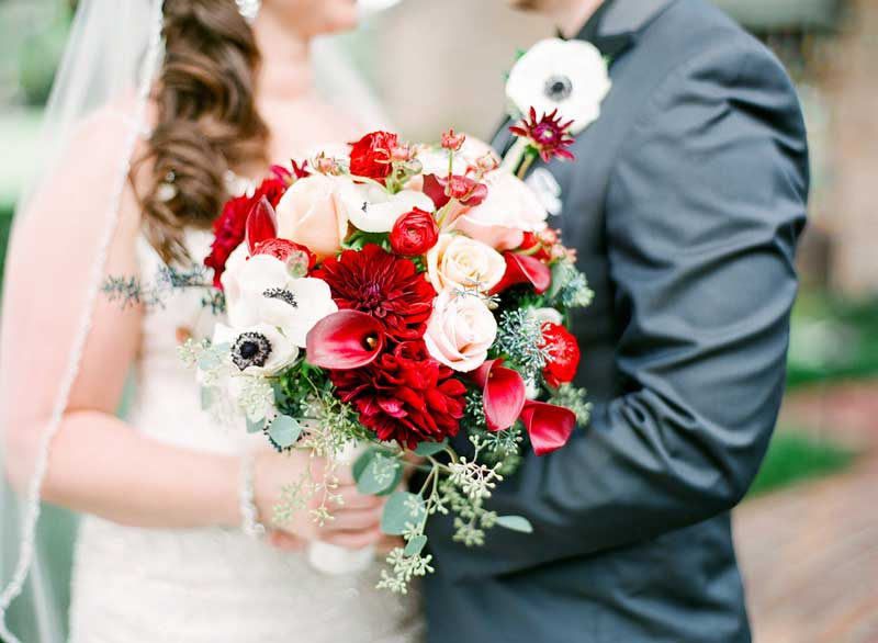 bride looking at groom while holding red and white bouquet