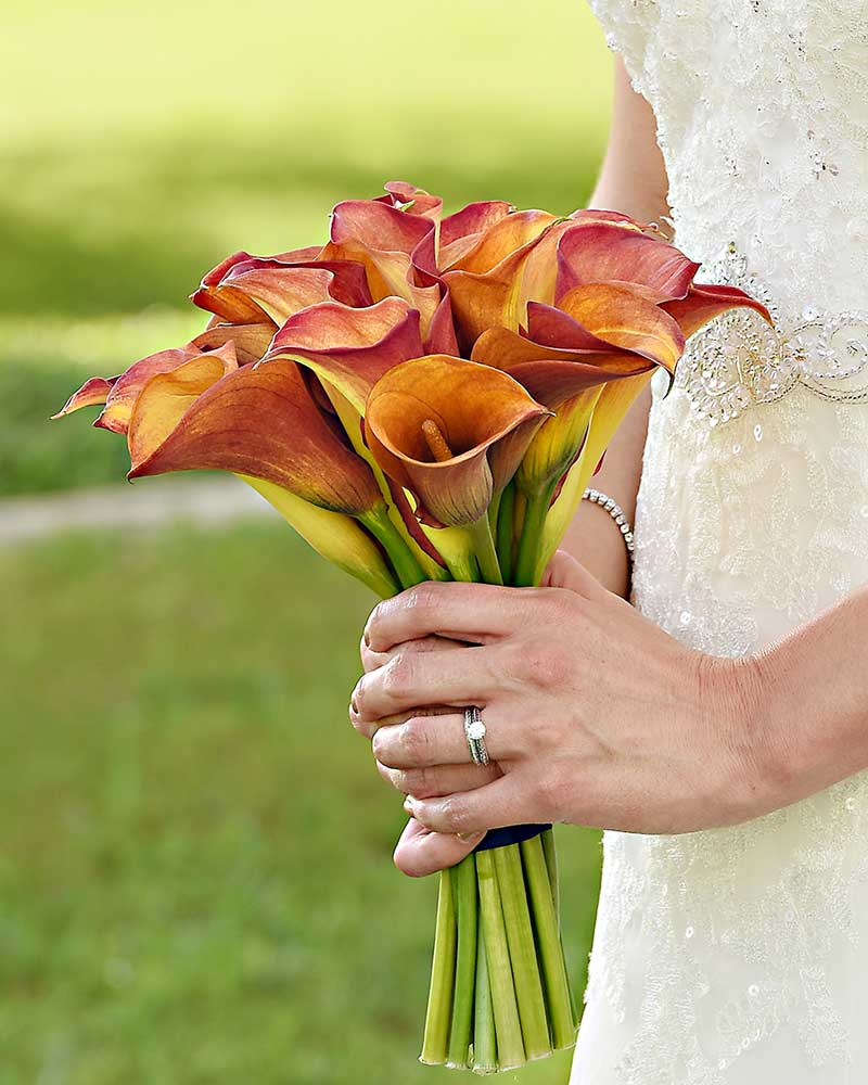 bride in grass holding red and orange calla lily bouquet