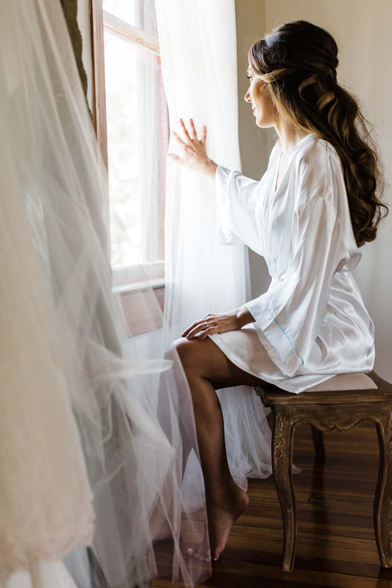 bride holding back curtains looking out window