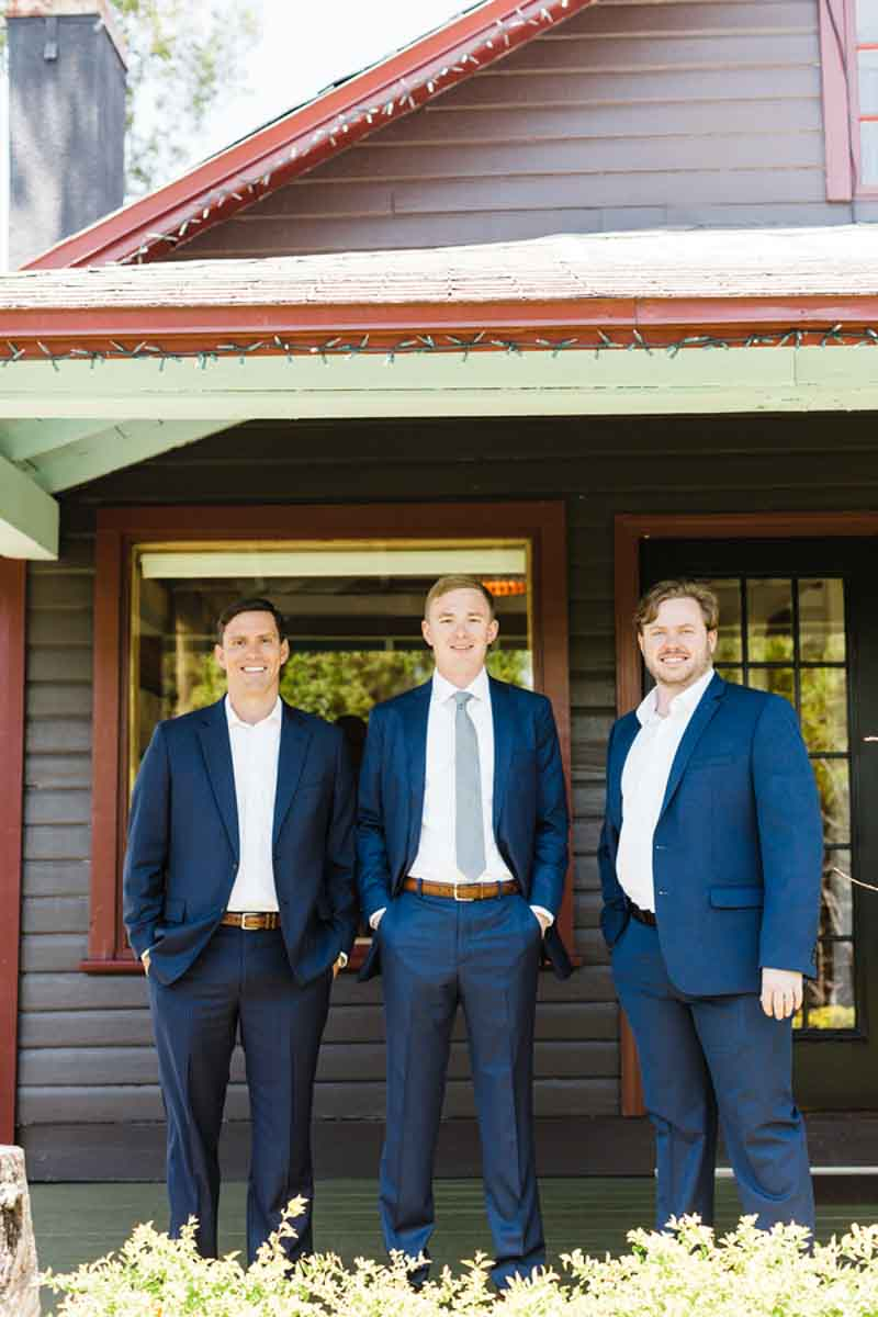 groom in navy suit under porch with groomsmen