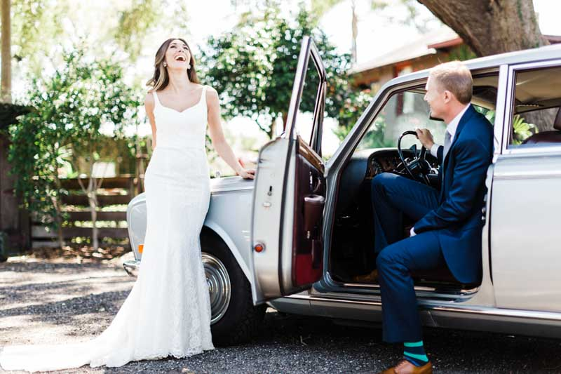 bride laughing in front of old car