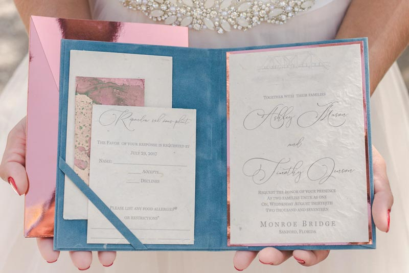 bride holding wedding invitation suite