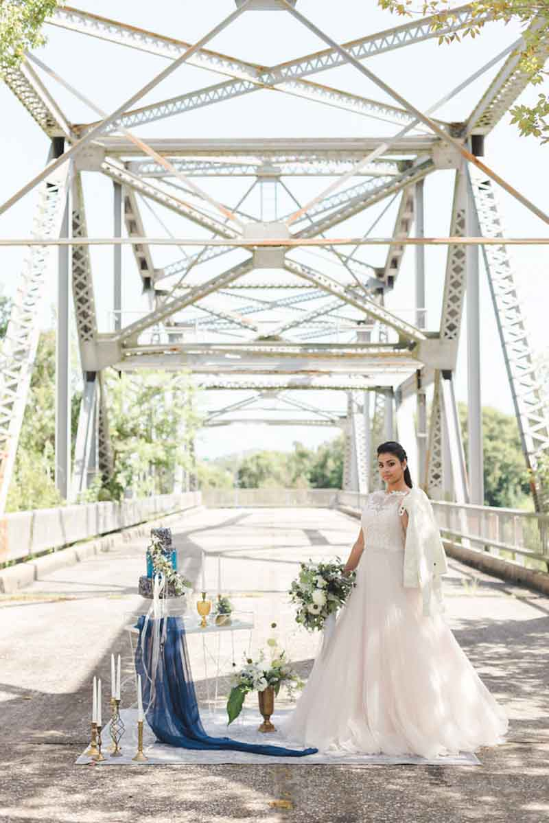 bride standing on bridge for industrial elegance wedding shoot