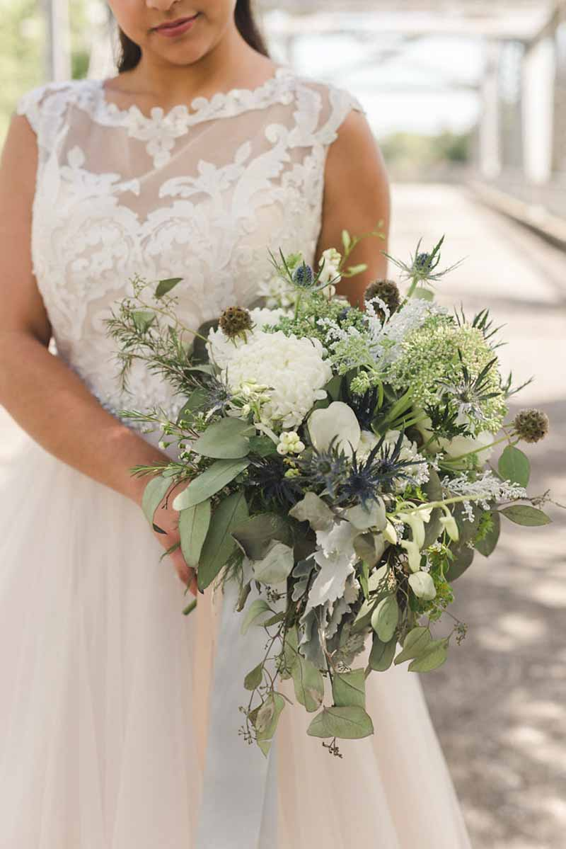 bride holding bouquet with greenery and thistles